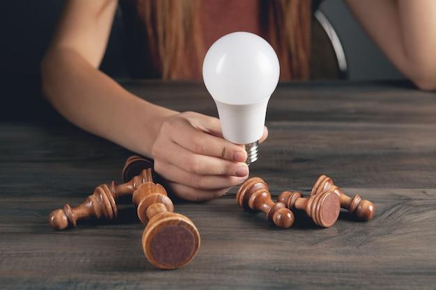 Mulher segurando uma lâmpada perto de peças de xadrez