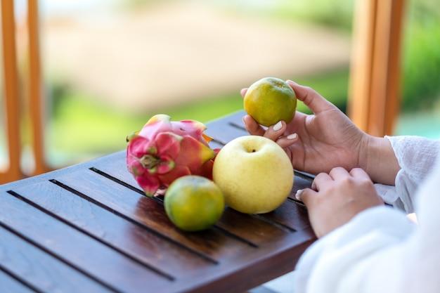 Mulher segurando uma laranja com pêra e fruta do dragão em uma pequena mesa de madeira