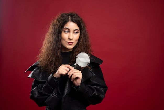 Mulher segurando uma lente de aumento