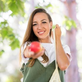 Mulher segurando uma maçã na frente