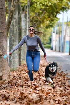 Mulher segurando uma máscara cirúrgica e um lindo cachorro correndo em folhas secas na rua.