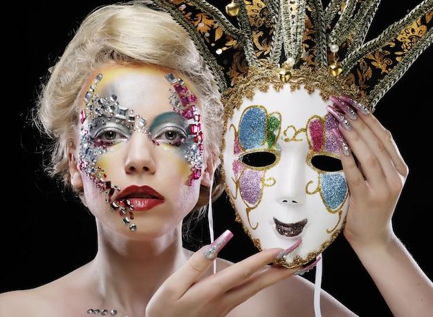 Mulher segurando uma máscara com maquiagem artística