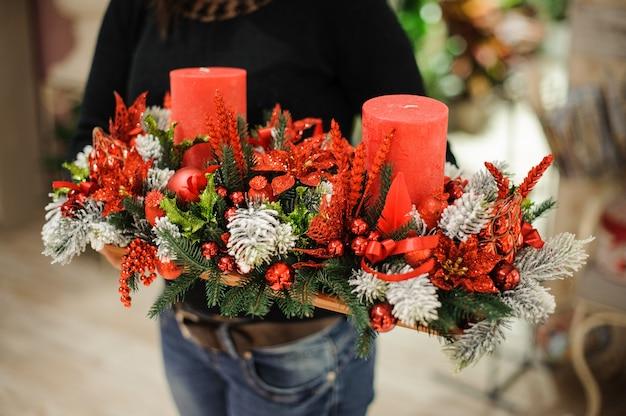 Mulher segurando uma mesa decorativa composição de natal feita de abeto, velas vermelhas, flores e bolas na placa de madeira