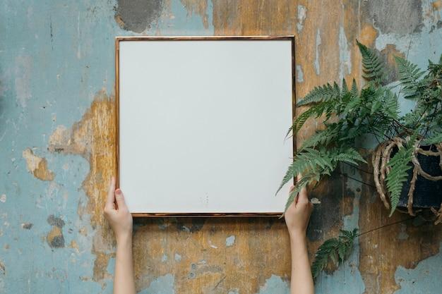 Mulher segurando uma moldura em branco contra uma parede suja