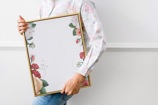Mulher segurando uma moldura floral