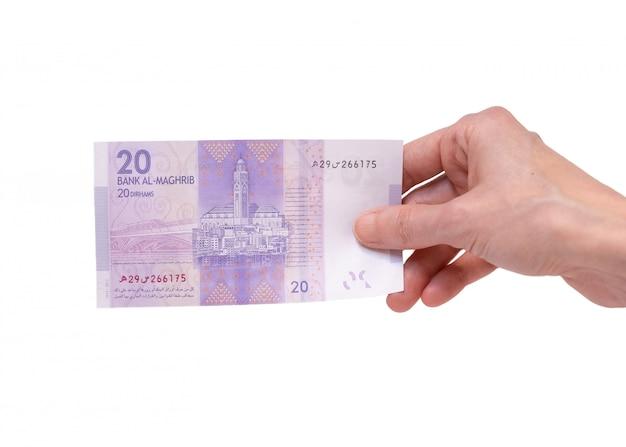Mulher segurando uma nota de 20 dirham moroccon na mão em um branco