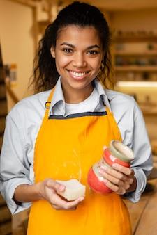 Mulher segurando uma panela de barro, tiro médio