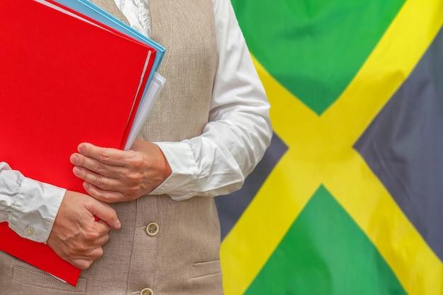 Mulher segurando uma pasta vermelha com a bandeira da jamaica atrás