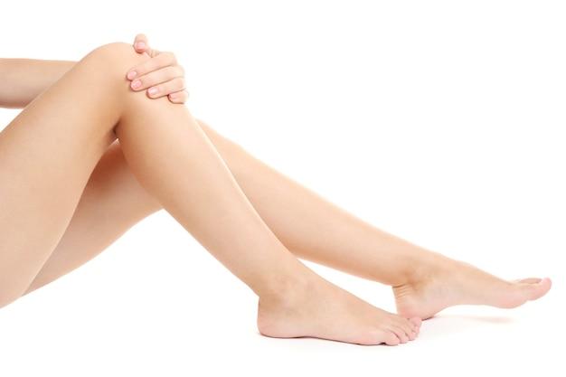 Mulher segurando uma perna dolorida, isolada no branco