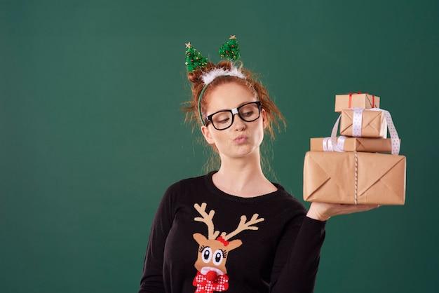 Mulher segurando uma pilha de presentes de natal