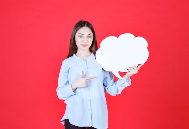 Mulher segurando uma placa de informações de forma de nuvem.