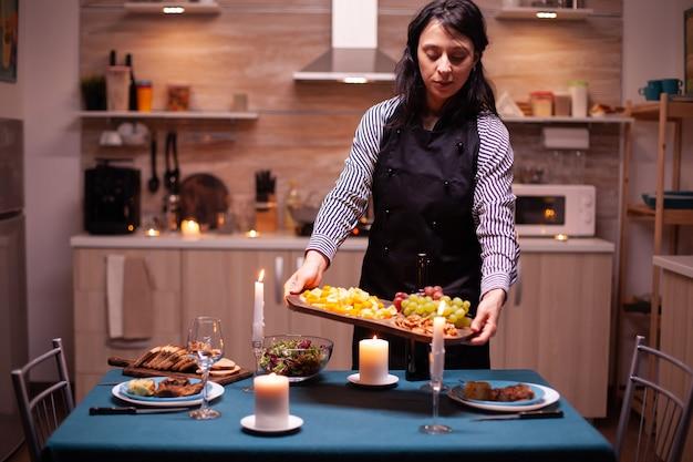 Mulher segurando uma placa de madeira com mistura de uvas e queijo, enquanto cozinha o jantar romântico. jovem senhora caucasiana cozinhando para o marido um jantar romântico, esperando na cozinha.