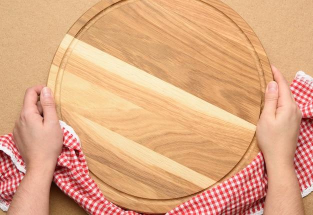 Mulher segurando uma placa redonda de madeira para pizza vazia na mão, corpo sobre um fundo marrom, vista superior