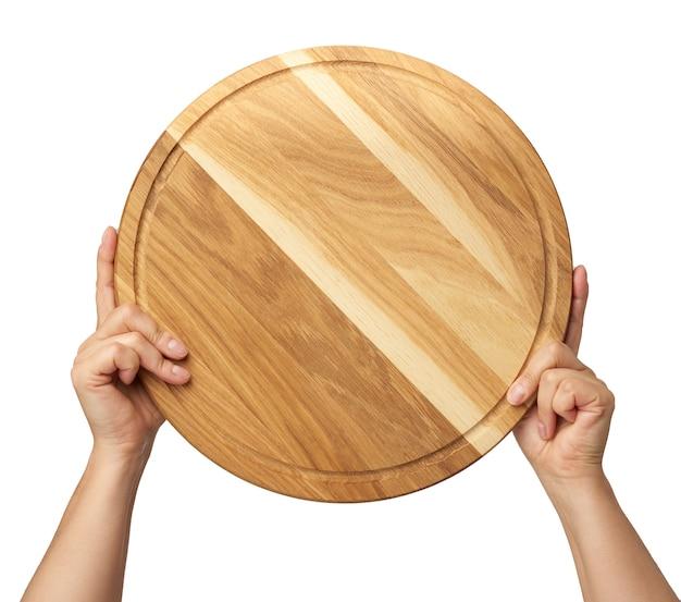 Mulher segurando uma placa redonda de madeira para pizza vazia