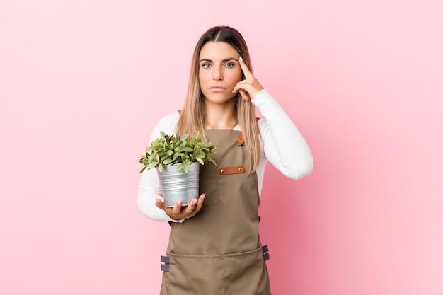Mulher segurando uma planta em estúdio