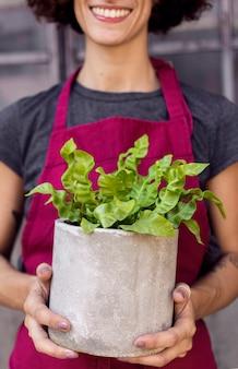 Mulher segurando uma planta em um pote branco close-up