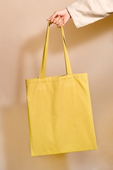 Mulher segurando uma sacola amarela