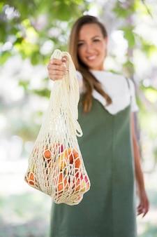 Mulher segurando uma sacola biodegradável com guloseimas