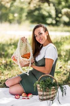 Mulher segurando uma sacola com lanches saudáveis