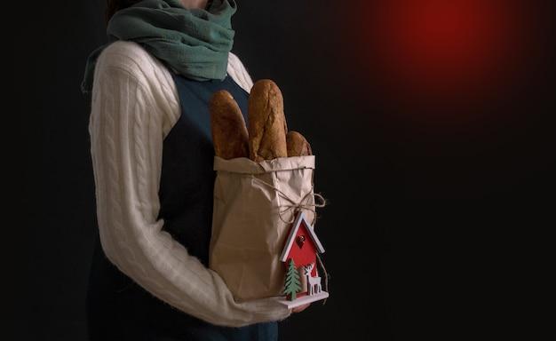 Mulher segurando uma sacola de compras com pão para o feriado de ano novo ou conceito de entrega de natal