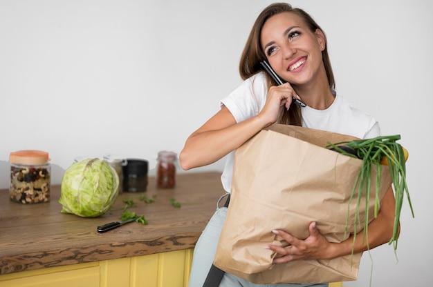 Mulher segurando uma sacola de compras enquanto fala ao telefone