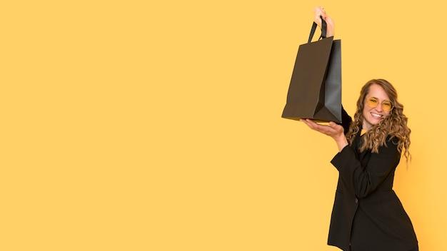 Mulher segurando uma sacola de compras preta copie o espaço