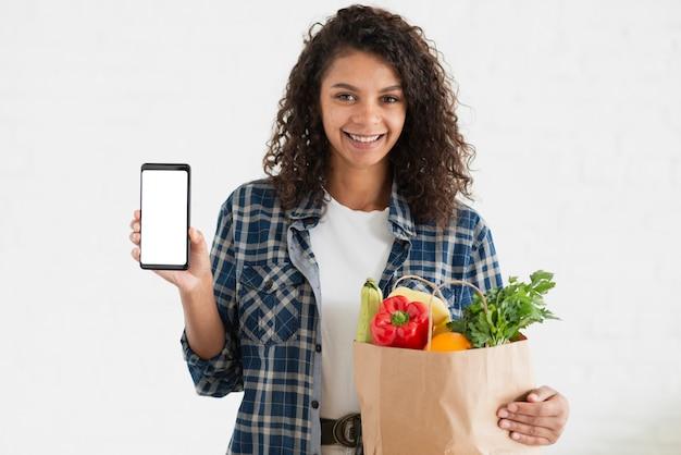 Mulher segurando uma sacola de legumes e um telefone simulado