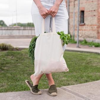 Mulher segurando uma sacola orgânica com parley e endro