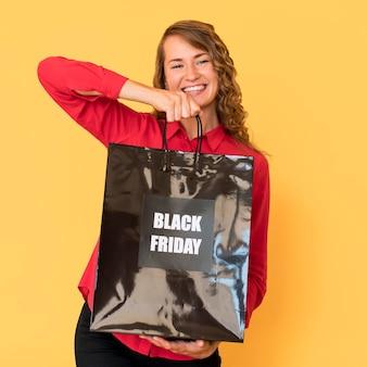 Mulher segurando uma sacola preta de compras da sexta-feira