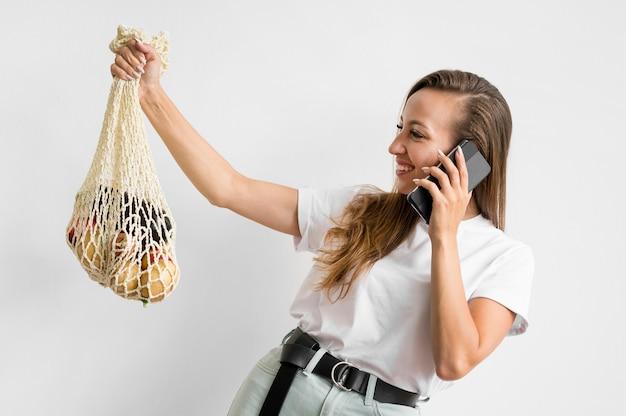 Mulher segurando uma sacola reciclável enquanto fala ao telefone
