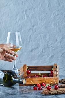 Mulher segurando uma taça de vinho branco e uma caixa de madeira com cerejas na superfície azul