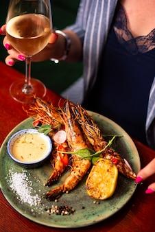 Mulher segurando uma taça de vinho com deliciosos camarões lagostins em restaurante