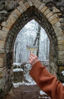 Mulher segurando uma taça de vinho no fundo de um castelo medieval na neve