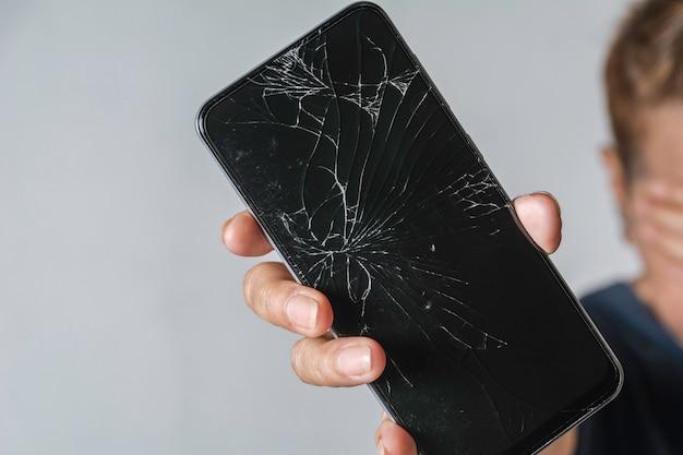 Mulher segurando uma tela de toque quebrado do telefone inteligente na mesa cinza.