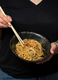 Mulher segurando uma tigela de macarrão de frutos do mar chinês com gergelim