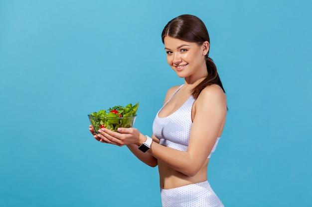 Mulher segurando uma tigela grande com salada de legumes fresca, olhando para a câmera com um sorriso, nutrição saudável