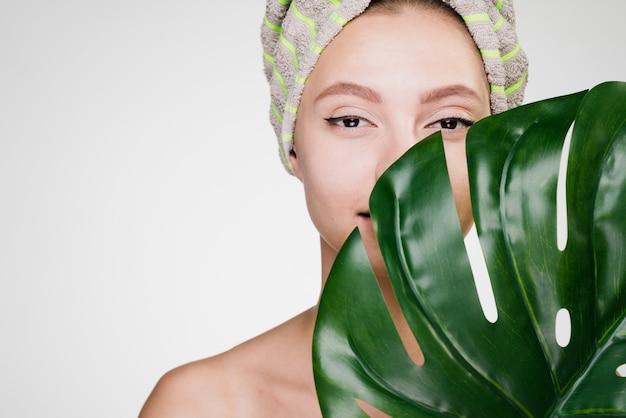 Mulher segurando uma toalha na cabeça, segurando uma folha grande