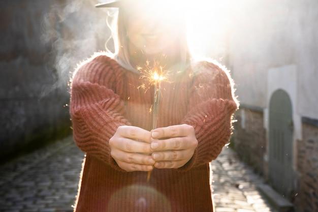 Mulher segurando uma vara de brilho