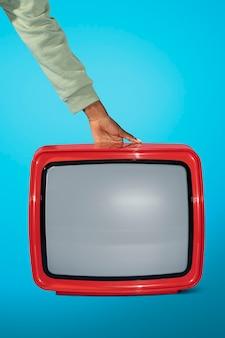 Mulher segurando uma velha televisão vermelha