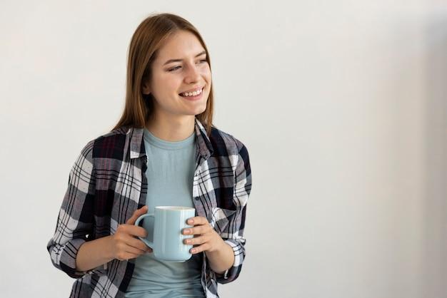 Mulher segurando uma xícara de café azul