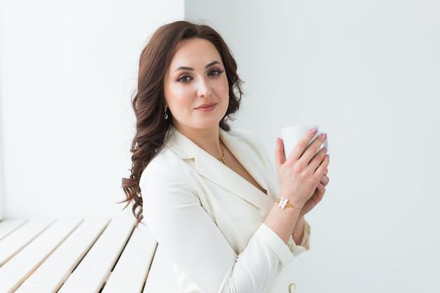 Mulher segurando uma xícara de café branca. com uma bela manicure. bebida, moda, manhã