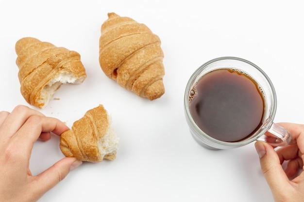 Mulher segurando uma xícara de café e croissant