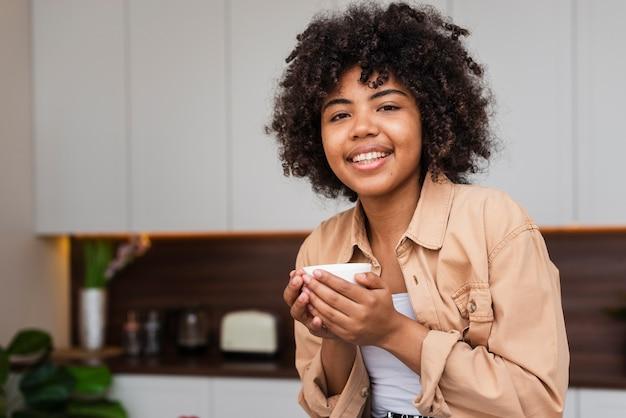 Mulher segurando uma xícara de café e olhando para o fotógrafo