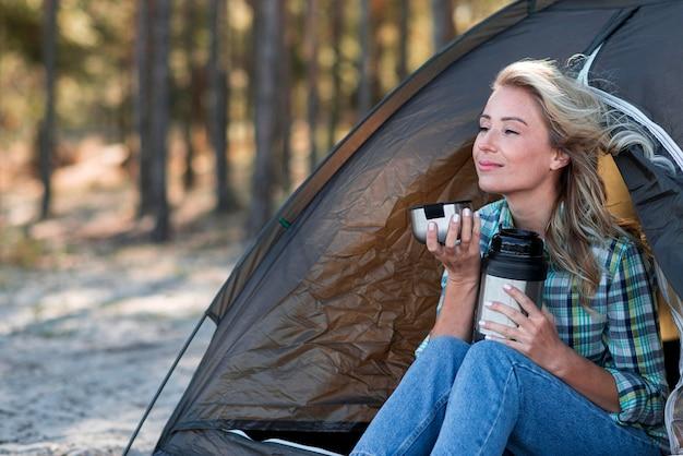 Mulher segurando uma xícara de café e sentada na barraca