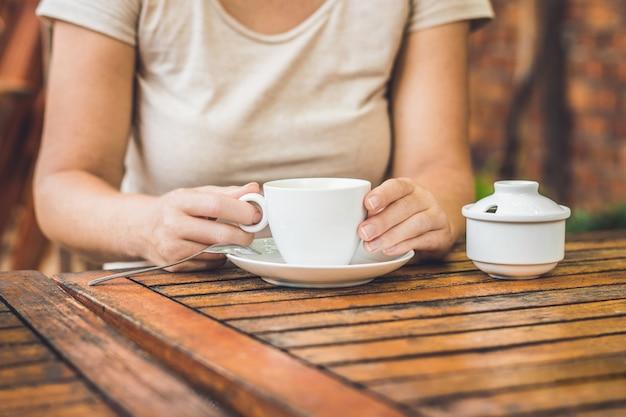 Mulher segurando uma xícara de café em uma cafeteria ao ar livre