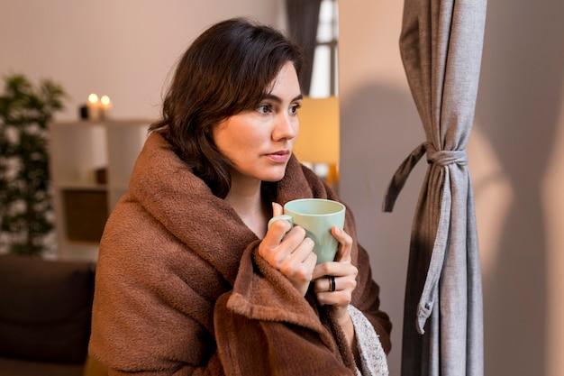 Mulher segurando uma xícara de café enquanto é coberta por um cobertor