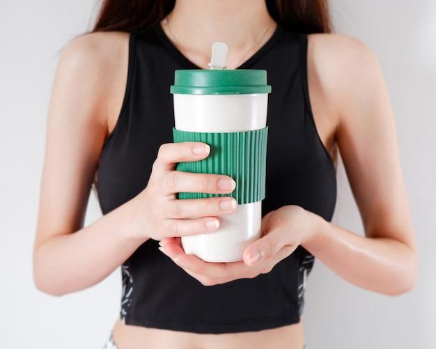 Mulher segurando uma xícara de café nas mãos com fundo de meninas de exercícios.