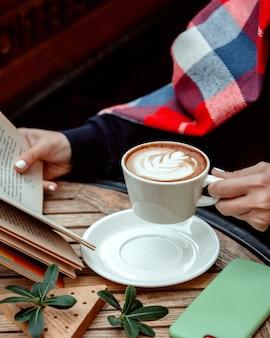 Mulher segurando uma xícara de cappuccino e lendo um livro
