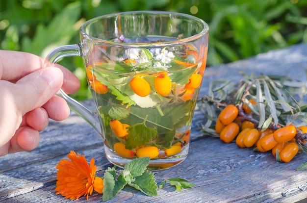 Mulher segurando uma xícara de chá de ervas com espinheiro-mar e calêndula em uma mesa de madeira. estilo de vida saudável
