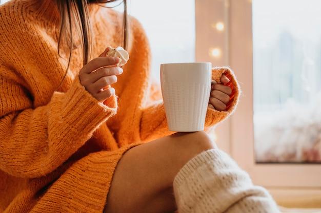 Mulher segurando uma xícara de chá dentro de casa